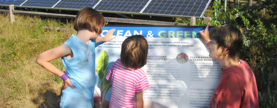 Woman and kids looking at the sign explaining a solar array