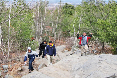 Boys hiking up boulder trail at Blue Hills Trailside Museum
