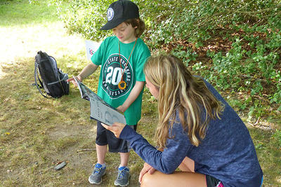 A counselor and camper using a field guide at North River