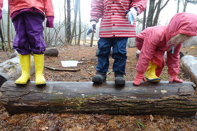 Preschoolers in raincoats playing on a log