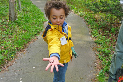 A young boy showing off the worm he found in spring at Blue Hills Trailside Museum