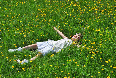 Child laying in grassy flower field © April Churchill