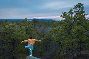 Woman in yoga pose balanced on rock that overlooking conservation land in Essex, MA © Davey Walters