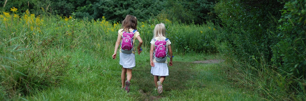 Two girls with backpacks on a trail © Lisa Roberts