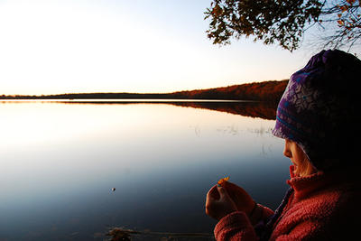 Young girl in winter gear examines a leaf by the edge of a lake © Paul Blankman