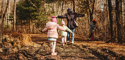 Family playing balancing game on a trail in fall at Moose Hill Wildlife Sanctuary