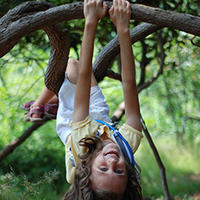 Girl hanging from tree © Lisa Roberts
