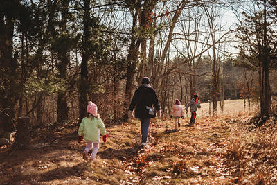 Parent with children of different ages walking on a trail in late fall