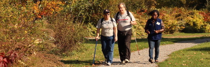 A Mass Audubon staff member walking with visitors on an accessible trail