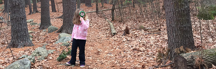 A child exploring the outdoors at Broadmoor Wildlife Sanctuary