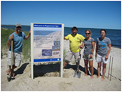 Staff and volunteers erect sign at Popponessett Beach.