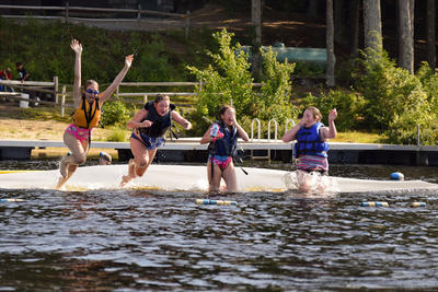 Four campers jumping into the water at Wildwood Overnight Camp
