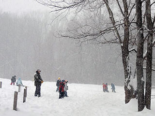People playing in the snow at Arcadia Wildlife Sanctuary