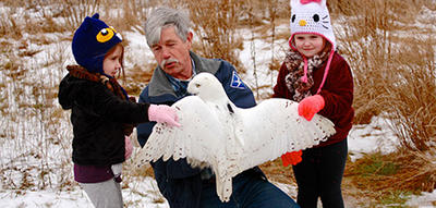 Norman Smith with a snowy owl and his grandchildren