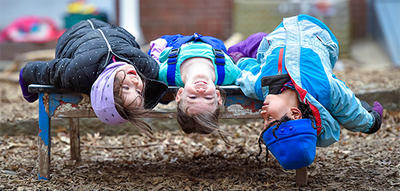 Preschoolers in winter coats laying on bench