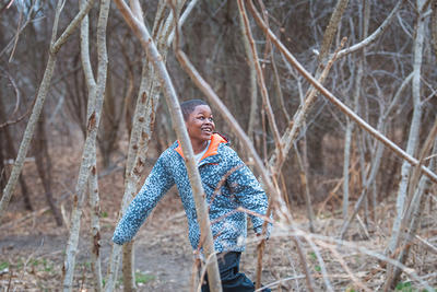 Young boy laughing while running through winter trees at Boston Nature Center