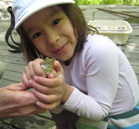 Girl with a frog in her hands
