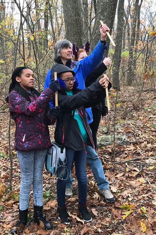 Students learning how to measure tree height