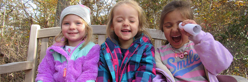 Three FN preschoolers laughing on a bench in fall