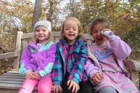 Three FN preschoolers laughing on a bench in fall 750