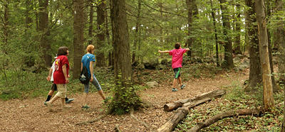 family walking on wooded trail at Habitat in summer