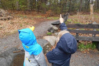 Two kids wearing fall jackets pointing up at something on a trail at Habitat Education Center