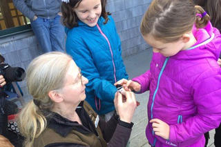 Deb La Roy helping kids release a banded chickadee