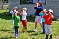 Young kids learning to use binoculars