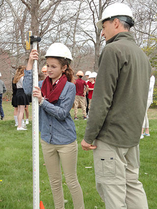 Ian Ives shows student how to measure the depth