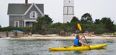 Woman kayaking by lighthouse