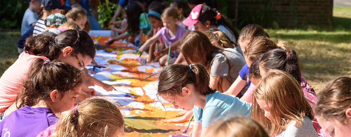 MABA campers painting a long mural on paper