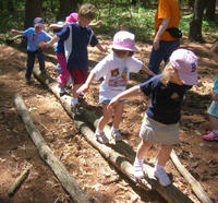 Children playing on logs at Moose Hill Wildlife Sanctuary