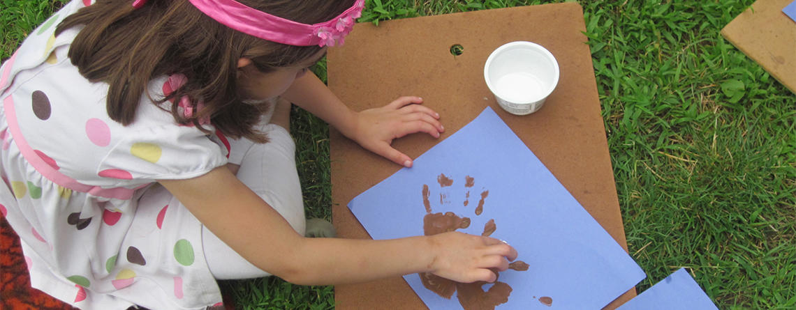 Girl doing outdoor nature craft in summer at Moose Hill