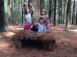Kids playing in the woods at Moose Hill Wildlife Sanctuary