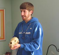 A teacher naturalist from Moose Hill Wildlife Sanctuary shows an animal skull to a school group