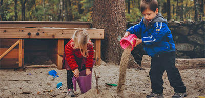 Preschoolers playing with sand in late fall