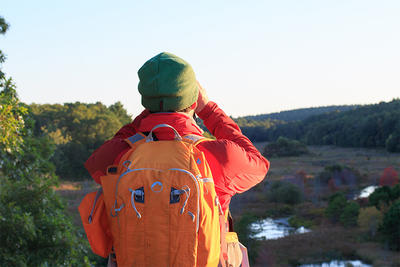 A fall hiker using binoculars to take in the view at Tidmarsh Wildlife Sanctuary
