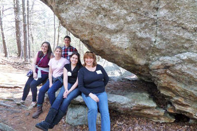 Group of teachers under a glacial boulder