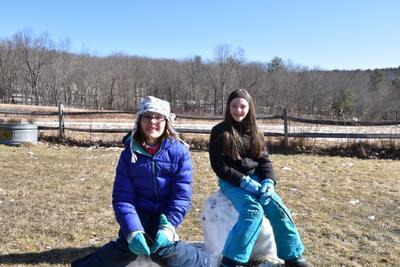 Kids sitting on melting snowmen during school vacation week at Wachusett Meadow Wildlife Sanctuary