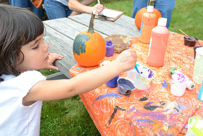 Young child painting a pumpkin during Hey Day at Wachusett Meadow