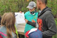 Wellfleet Bay educator showing students a map