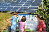 Woman with children at solar energy sign
