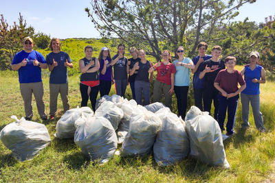 Teens standing proudly behind a pile of trash bags after cleaning up a natural area