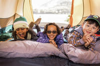 Three kids laughing inside a tent