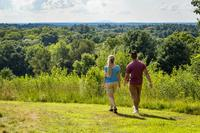 Woman & man walking by overlook at Drumlin Farm Wildlife Sanctuary in summer