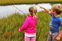 Two children exploring a marsh at Felix Neck Wildlife Sanctuary