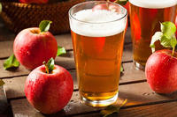 Glass of hard cider with apples