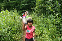 Oak Knoll camper proudly holding up a bug collection jar