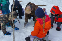 Students investigate animal tracks in winter during a school program