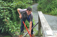 Volunteer Erich Wilmot works to clear blockage on the first spillway